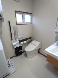 トイレは横からの介助が出来る配置に。病気で力が入らないことを考え、前方手すりを取り付け。