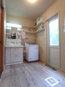 リフォーム後の洗面脱衣場。洗面化粧台を交換。床は無垢杉フローリング仕上げ。壁は珪藻土仕上げ。収納棚を造作。窓を勝手口に。