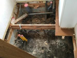 床を解体。床下調湿工事を行うので根太をすべて撤去しました。便器の排水芯の関係、およびハイドロセラの割り付けの関係で、排水位置を変更しています。